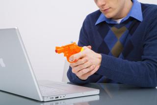 Man-pointing-gun-at-laptop_BFPsCVRHj